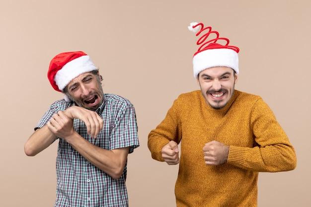 Widok z przodu dwóch facetów z czapkami mikołaja, jeden trzymający rękę z bólem na beżowym tle na białym tle