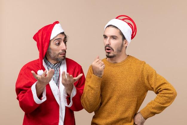 Widok z przodu dwóch mężczyzn w czapkach mikołaja myśli o czymś na beżowym tle na białym tle