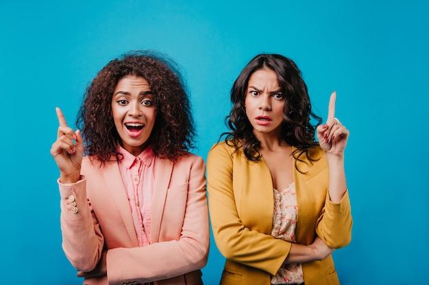 Widok z przodu dwóch młodych kobiet wyrażających emocje na niebieskiej ścianie