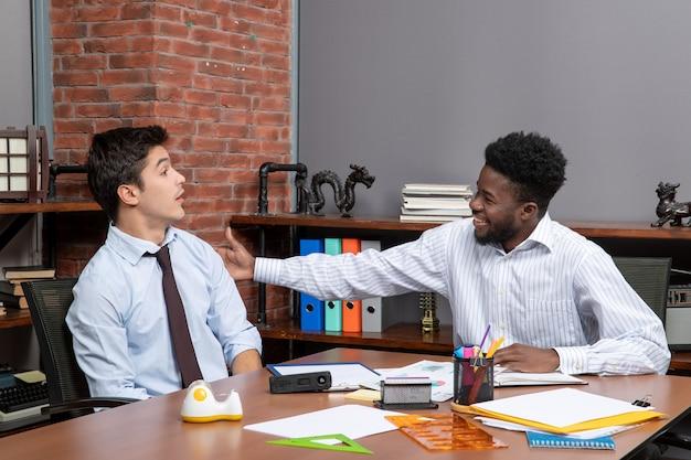 Widok z przodu dwóch partnerów biznesowych w stroju wizytowym pracujących w biurze