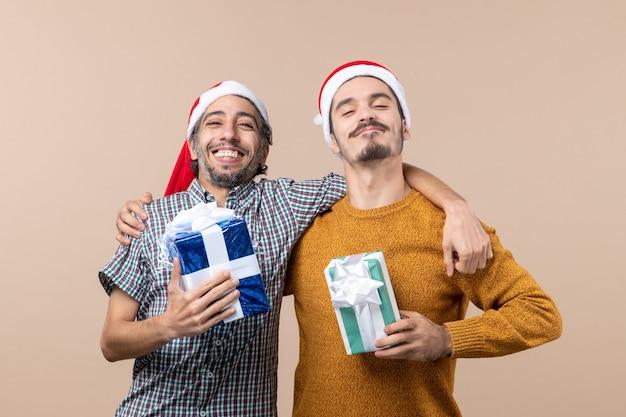 Widok z przodu dwóch pewnych siebie facetów przytulających i trzymających świąteczne prezenty na beżowym tle na białym tle