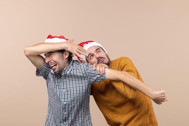 Widok z przodu dwóch przestraszonych facetów w czapkach mikołaja, jeden ukrywający twarz, a drugi na beżowym tle na białym tle