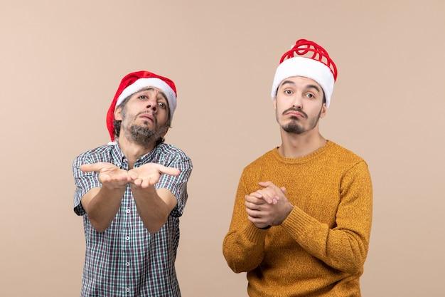 Widok z przodu dwóch przygnębionych facetów w czapkach mikołaja, jeden pokazuje coś na beżowym tle