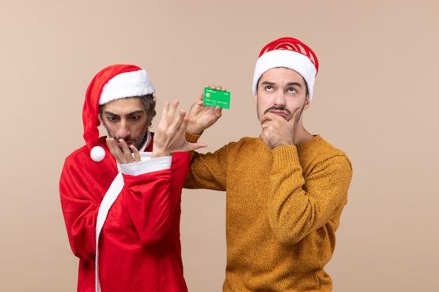 Widok z przodu dwóch przyjaciół, jeden w płaszczu mikołaja, patrząc na jego rękę, a drugi trzymający kartę na beżowym tle na białym tle