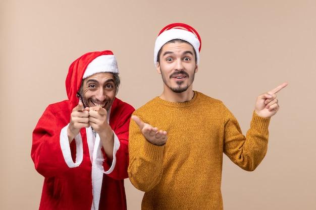 Widok z przodu dwóch przyjaciół z czapkami mikołaja obaj wskazujący palec pokazujący aparat na beżowym na białym tle