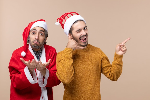 Widok z przodu dwóch przyjaciół z czapkami świętego mikołaja, jeden dzwoniący do mnie znak telefonu na beżowym tle na białym tle