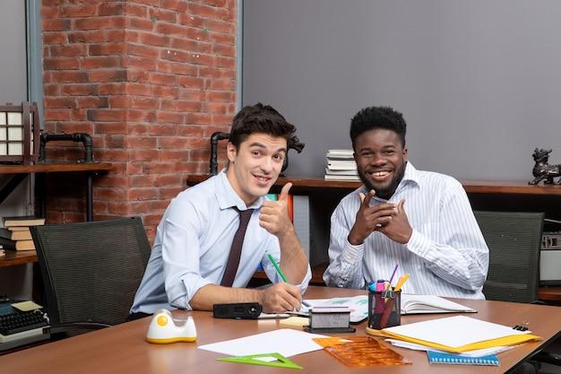 Widok z przodu dwóch szczęśliwych biznesmenów patrzących w kamerę, jeden z nich daje kciuk w górę