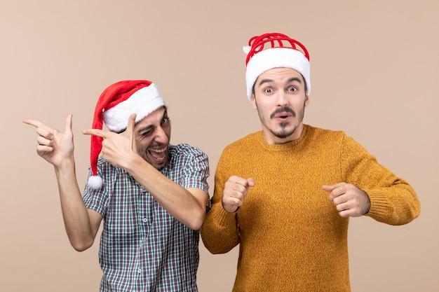 Widok z przodu dwóch szczęśliwych facetów w czapkach mikołaja, jeden z mrugniętymi oczami, a drugi z ciekawskimi oczami na beżowym tle