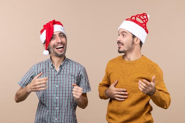 Widok z przodu dwóch szczęśliwych facetów z czapkami mikołaja śmiejącymi się na beżowym tle na białym tle