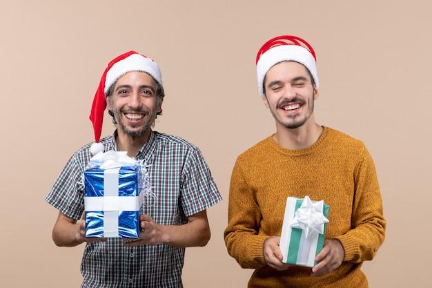 Widok z przodu dwóch szczęśliwych mężczyzn w czapkach mikołaja i trzymających prezenty świąteczne na beżowym tle na białym tle