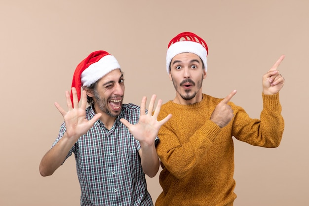 Widok z przodu dwóch szczęśliwych mężczyzn z czapkami mikołaja, jeden pokazujący coś, a drugi przybijający piątkę na odosobnionym tle