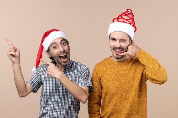 Widok z przodu dwóch uśmiechniętych facetów w czapkach mikołaja, jeden pokazuje coś, a drugi sprawia, że zadzwoń do mnie znak telefonu na beżowym na białym tle