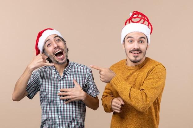 Widok z przodu dwóch uśmiechniętych facetów w czapkach świętego mikołaja, jeden robiący zadzwoń do mnie znak telefonu, a drugi wskazujący palec pokazujący go na beżowym tle