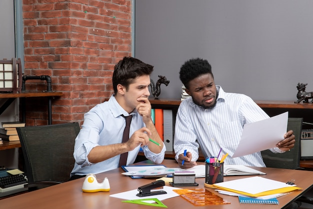 Widok z przodu dwóch uważnych biznesmenów satysfakcjonujących wspólną pracę