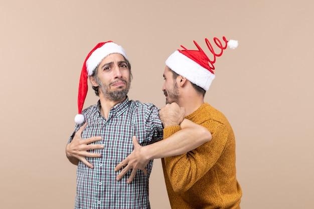 Widok z przodu dwóch wzburzonych mężczyzn w czapkach mikołaja, jeden trzyma drugich za ramiona na odosobnionym tle
