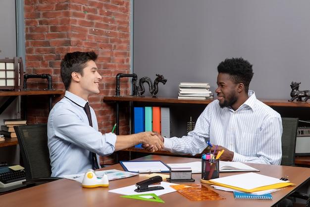 Widok z przodu dwóch zadowolonych biznesmenów siedzących przy biurku, ściskających ręce w biurze