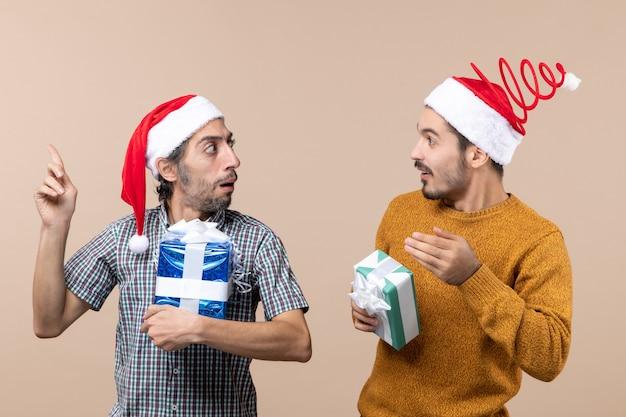 Widok z przodu dwóch zainteresowanych facetów pokazujących sobie nawzajem prezenty na beżowym tle