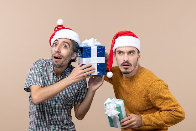 Widok z przodu dwóch zainteresowanych facetów w czapkach mikołaja i zwracających uwagę na prezenty świąteczne na beżowym na białym tle