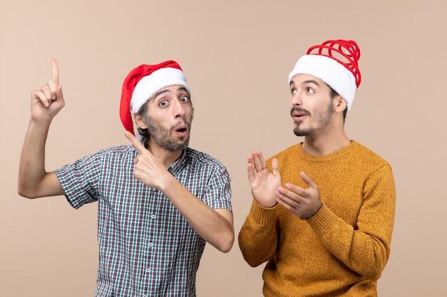 Widok z przodu dwóch zainteresowanych facetów w czapkach mikołaja, jeden pokazujący coś drugiemu na beżowym tle