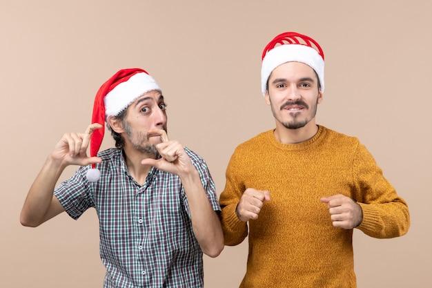 Widok z przodu dwóch zainteresowanych facetów w czapkach mikołaja, jeden robiący znak aparatu rękami na beżowym na białym tle
