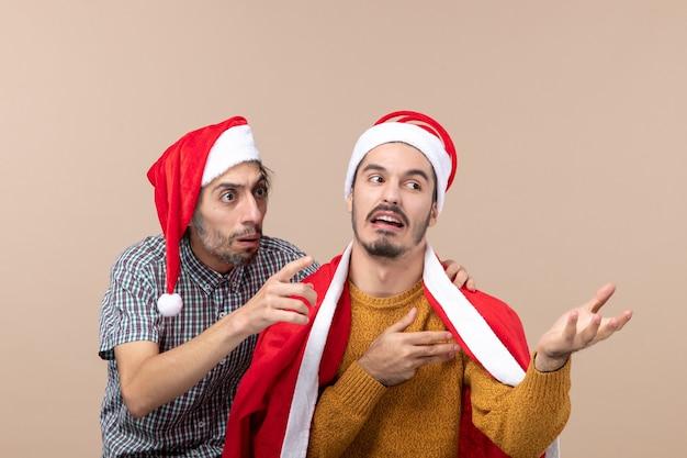 Widok z przodu dwóch zainteresowanych facetów w czapkach mikołaja, patrząc na coś na beżowym tle