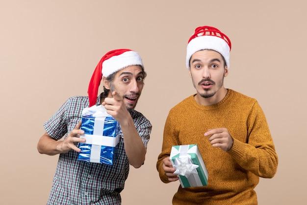 Widok z przodu dwóch zainteresowanych facetów wskazuje palcem coś i trzyma świąteczne prezenty na beżowym tle