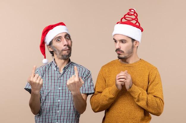 Widok z przodu dwóch zainteresowanych mężczyzn w czapkach mikołaja, jeden patrząc na drugiego na beżowym tle na białym tle