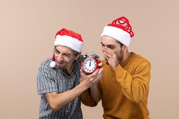 Widok z przodu dwóch zaniepokojonych mężczyzn chcących wyłączyć zegar na beżowym tle na białym tle