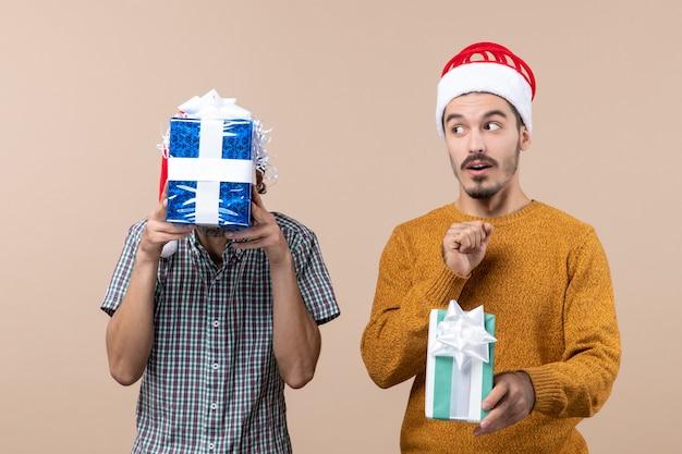 Widok z przodu dwóch zaskoczonych facetów w czapkach mikołaja trzymających świąteczne prezenty jeden zakrywający twarz prezentem na beżowym tle na białym tle