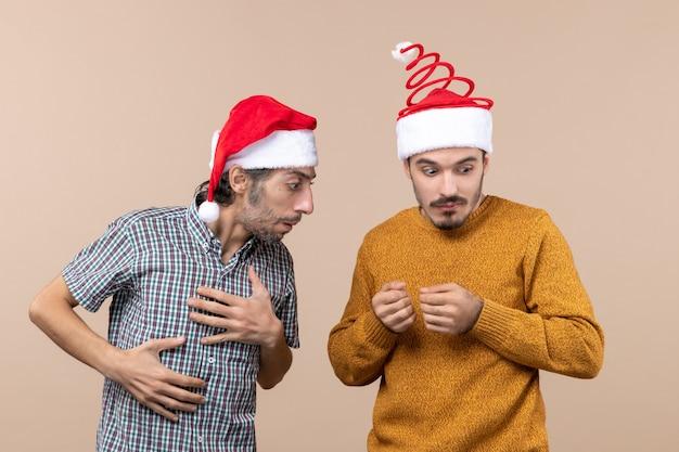 Widok z przodu dwóch zdezorientowanych facetów z czapkami mikołaja jeden patrzy na innych ręką na beżowym tle na białym tle