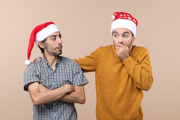 Widok z przodu dwóch zdumionych facetów w czapkach mikołaja. jeden kładzie rękę na ramieniu drugiego na beżowym tle