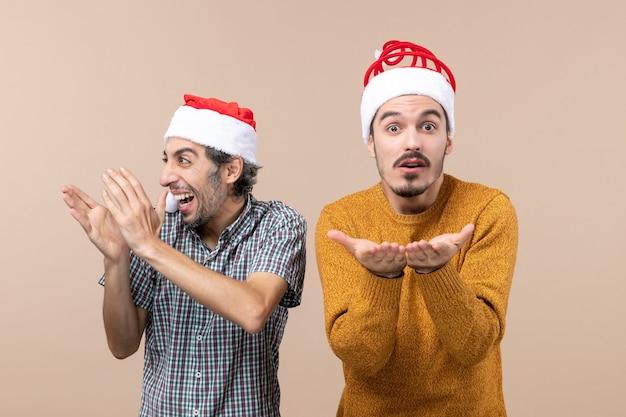 Widok z przodu dwóch zdumionych facetów w czapkach mikołaja, jeden klaszczący w dłonie, a drugi otwierający ręce, stojąc na beżowym tle
