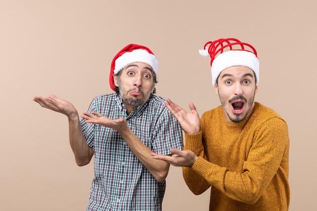 Widok z przodu dwóch zdumionych facetów w czapkach mikołaja pokazujących coś beżowego na białym tle