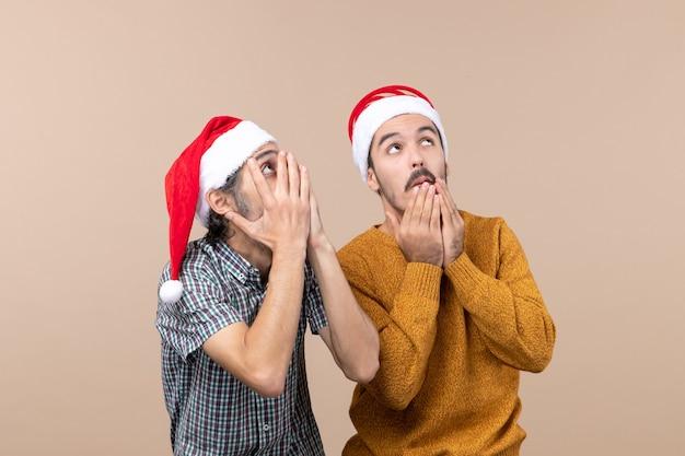 Widok z przodu dwóch zdumionych mężczyzn w czapkach mikołaja, patrząc na coś z wielkim zainteresowaniem na odosobnionym tle