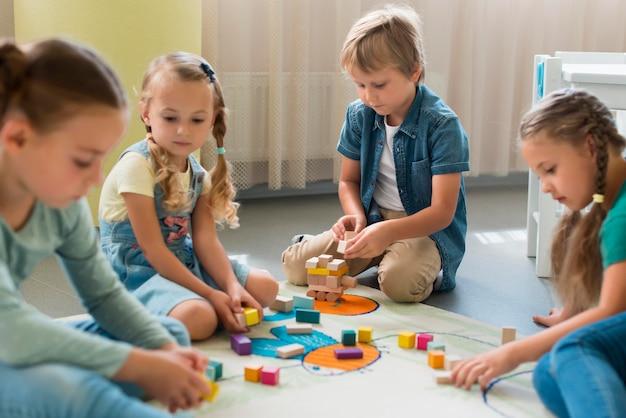 Widok z przodu dzieci bawiące się razem w przedszkolu