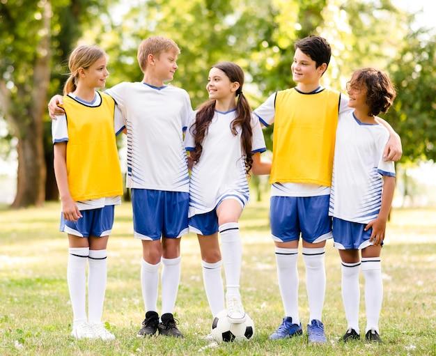 Widok z przodu dzieci w piłkarskiej odzieży sportowej, patrząc na siebie