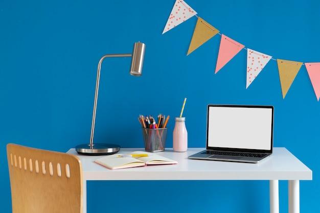 Widok z przodu dziecięcego biurka z kolorowymi ołówkami i laptopem
