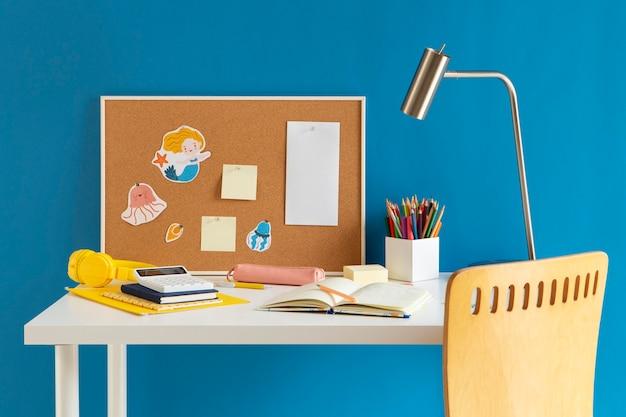 Widok z przodu dziecięcego biurka z lampką i notebookiem
