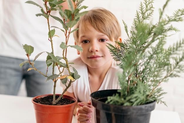 Widok z przodu dziecka w domu z tatą patrząc na rośliny