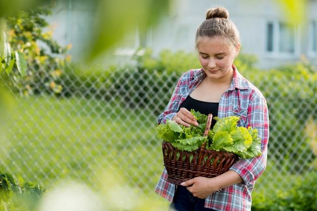 Widok z przodu dziewczyna trzyma kosz sałaty