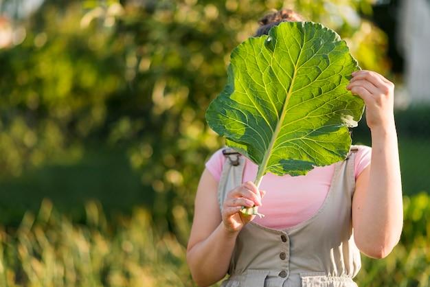 Widok z przodu dziewczyna trzyma liść sałaty