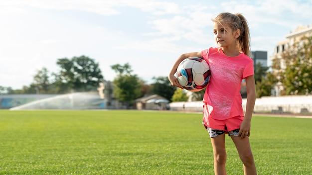 Widok z przodu dziewczynka gospodarstwa piłkę