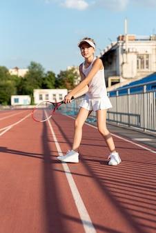Widok z przodu dziewczynka gospodarstwa rakieta tenisowa