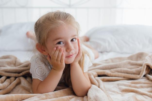 Widok z przodu, dziewczynka leży w łóżku, rano patrzy podejrzliwie w kamerę
