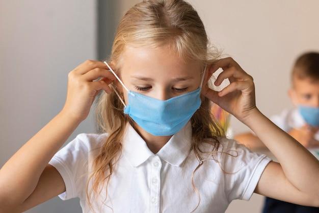 Widok z przodu dziewczynka zakładanie maski na twarz