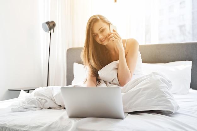 Widok z przodu dziewczyny siedzącej w łóżku ze smartfonem przyciśniętym do ucha