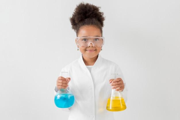 Widok z przodu dziewczyny w okularach ochronnych i fartuch gospodarstwa rurki