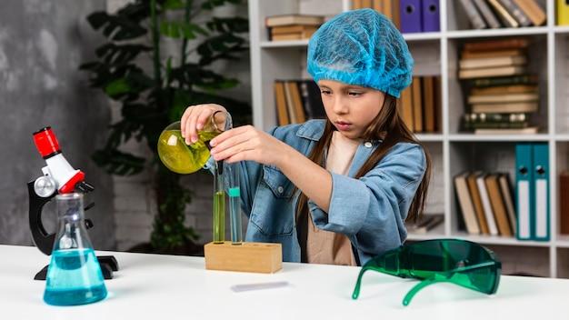 Widok z przodu dziewczyny z siatką na włosy robi eksperymenty naukowe z probówkami