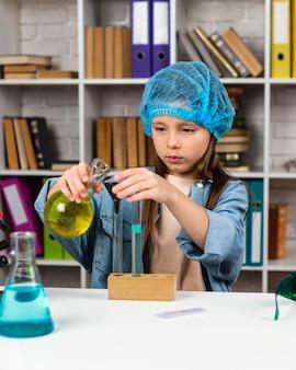 Widok z przodu dziewczyny z siatką na włosy robi eksperymenty naukowe