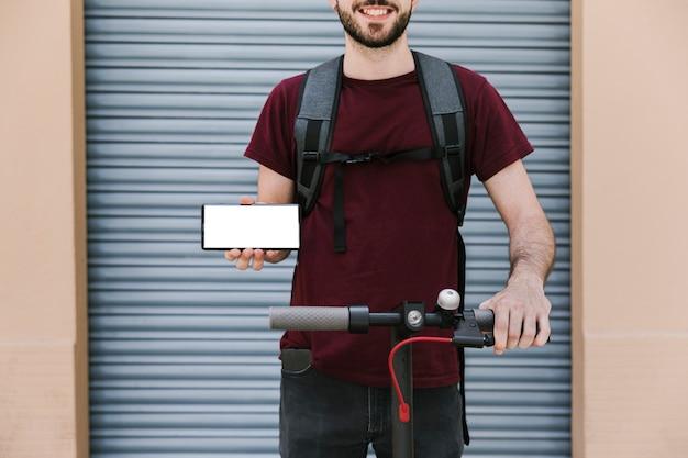 Widok z przodu e-hulajnoga jeźdźca z makietą smartfona